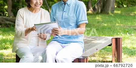 タブレットを操作するシニア女性と介護士 66792720