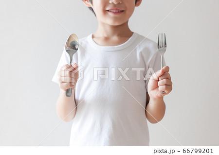 フォークとスプーンを持つ笑顔の子供 66799201