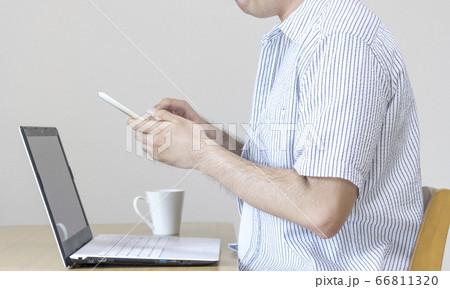 自宅で私服でスマートフォンで仕事をしている男性。在宅勤務、副業のイメージ 66811320