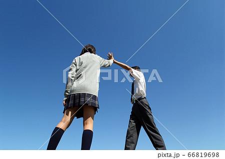 青空の下ハイタッチをする高校生男女 66819698