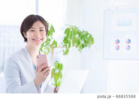 ビジネス スマホを持ち微笑む若い女性 66835568