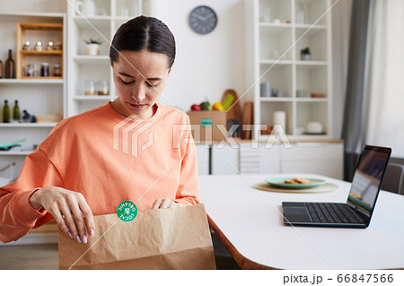 Woman unpacking package 66847566