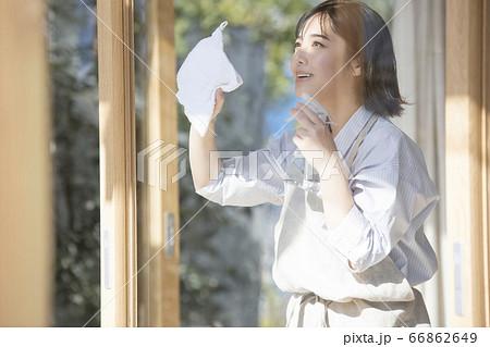 窓を掃除する若い女性 66862649