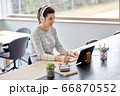 woman in headphones with tablet pc working at home 66870552