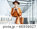 Young woman traveling with photo camera in the modern city 66936027