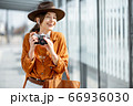Young woman traveling with photo camera in the modern city 66936030