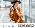 Young woman traveling with photo camera in the modern city 66936032