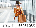 Young woman traveling with photo camera in the modern city 66936035