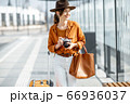 Young woman traveling with photo camera in the modern city 66936037