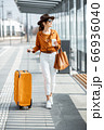 Young female traveler with a luggage at the transport stop 66936040