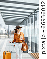 Young female traveler with a luggage at the transport stop 66936042