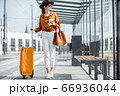 Young female traveler with a luggage at the transport stop 66936044