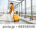 Young female traveler with a luggage at the transport stop 66936046