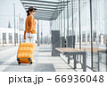 Young female traveler with a luggage at the transport stop 66936048
