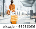 Young female traveler with a luggage at the transport stop 66936056