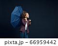 Little girl holds an umbrella, wind effect 66959442