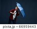 Boy with a scared face holds umbrella in studio 66959443