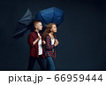 Boy and girl with umbrellas in studio, wind effect 66959444