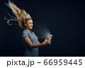 Woman looking on phone against powerful airflow 66959445