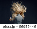 Woman standing against powerful airflow, back view 66959446