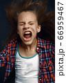 Little girl shouting in studio, developing hair 66959467