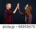 Little boy and girl beats the palms in studio 66959470