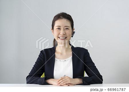 ヘッドセットをつけてカメラ目線のビジネスウーマン 66961787