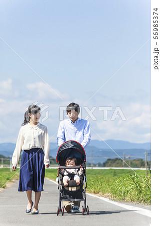 田園風景の遊歩道をベビーカーを押しながら散歩する若い夫婦 66985374