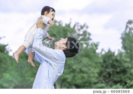 緑の樹木を背景に赤ちゃんを高く抱き上げる若いお父さん 66985669