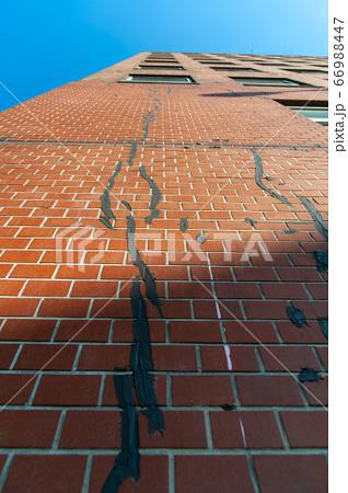 割れたレンガをコンクリートで修復している壁 66988447