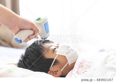 非接触式体温計で検温される男の子 66992107