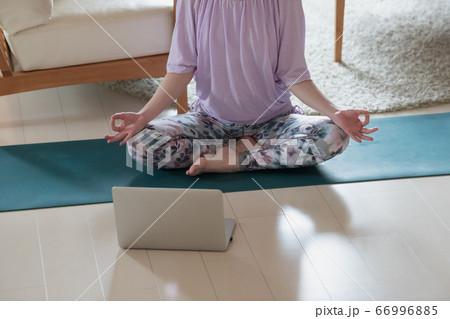 自宅でPCの前でオンラインヨガ(瞑想)をする日本人女性イメージ 66996885