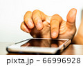 手でスマートフォンを操作している様子 66996928