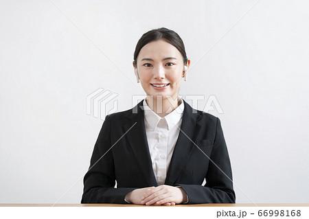 ワイヤレスヘッドホンをつけたカメラ目線のスーツ姿の若い女性 66998168