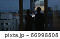 Couple using pad and enjoying view of evening city 66998808