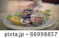 Pouring lemon juice on oysters 66998857