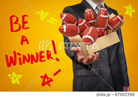 Anonymous businessman levitating box full of brown balls for American football that are flying out of it on amber background with title 'Be a Winner' 67002598