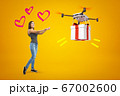 Happy young girl in casual clothes and three cute hearts around head, waiting for delivery drone to drop big gift on amber background. 67002600