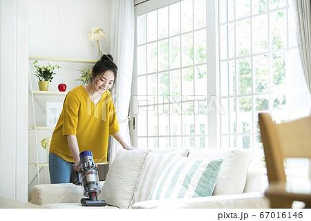 ソファーを掃除する若い女性 67016146