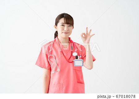 白バックのピンクの医療着を着てOKサインをする若い女性ドクターのポートレート 67018078