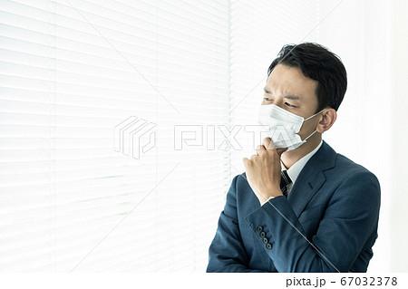 深刻そうに考えるマスクを着けた男性 感染症対策 67032378