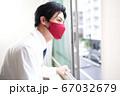 窓の外を見るマスク姿の男性 67032679