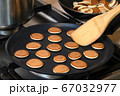 Tiny cereal pancakes frying in pan.  67032977