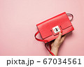 Red women's bag in hand on pink. Flat lay. View from above 67034561