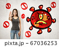 Young brunette girl making stop gesture with red angry cartoon germ drawn on white background 67036253