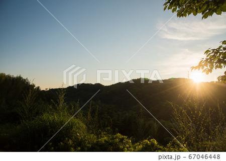 山から日の出した太陽に照らされた空と木 67046448