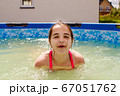 teen girl is swimming in a small pool 67051762