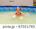 teen girl is swimming in a small pool 67051765