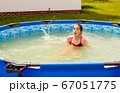 teen girl is swimming in a small pool 67051775