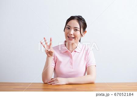 ワイヤレスイヤホンを付けてカメラ目線で話す女性 オンライン講師イメージ 67052184